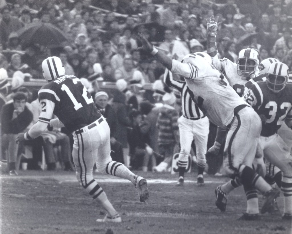 Joe Namath gets the pass off just before Ron McDole closes in.