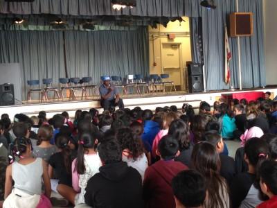 Dick Westmoreland addresses an auditorium full of children.